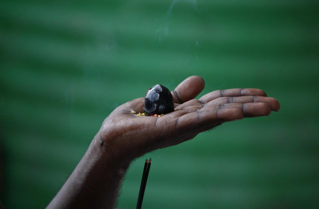 """A Hindu holy man waiting to register for the annual pilgrimage to the Himalayan cave shrine Amarnath, lights incense sticks as he worships a """"shivling"""" representing Lord Shiva, the Hindu god of destruction and regeneration, in Jammu, India, Tuesday, June 30, 2015. (Photo by Channi Anand/AP Photo)"""