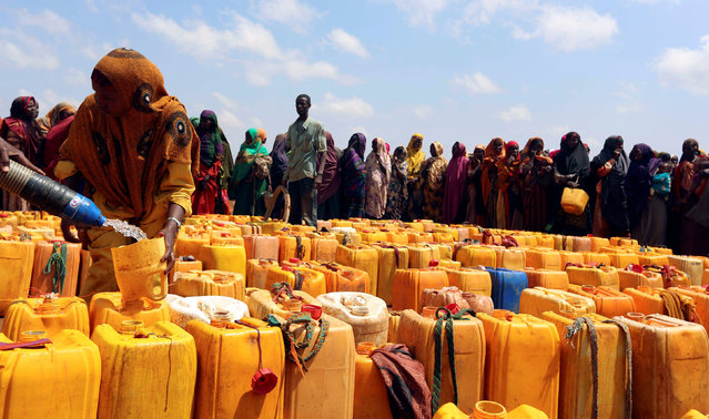 Internally displaced Somali women gather with their jerrycans to receive water at a distribution centre organized by a Qatar charity after fleeing from drought stricken regions in Baidoa, west of Somalia's capital Mogadishu, April 9, 2017. (Photo by Feisal Omar/Reuters)