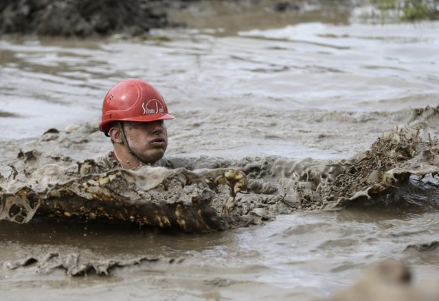 Participant wears a helmet as he swims in the cold and muddy water pool during the Strong Race competition near Tukums May 4, 2014. (Photo by Ints Kalnins/Reuters)