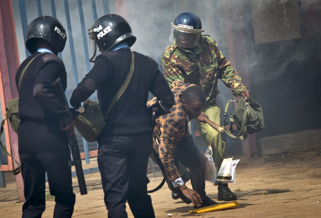 An opposition supporter is beaten with a wooden club by riot police as he tries to flee, during a protest in downtown Nairobi, Kenya Monday, May 16, 2016. (Photo by Ben Curtis/AP Photo)