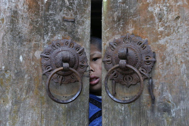 Xie Guobiao, 11, looks out of the door of his home in Daohui village of Lishui, Zhejiang province May 8, 2014. (Photo by William Hong/Reuters)