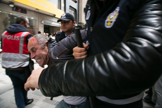 Turkish riot police arrest a protester seeking to defy a ban and march to Istanbul's Taksim square to celebrate May Day in Istanbul on May 1, 2017. Police tried to stop around 200 protesters in the Gayrettepe district on the European side of Istanbul who wanted to walk to the famous square in spite of the ban by city authorities. The protesters -- made up of left-wing groups -- unfurled anti-government banners against the result of the April 16 referendum, which handed President Recep Tayyip Erdogan expanded powers. (Photo by Gurcan Ozturk/AFP Photo)