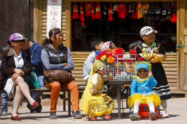 """""""Dwarf Empire"""" cast member Liu Jin Jin (center in yellow, aged 23) and Chen Jiang Chuan (right in blue, aged 18) watch the performance at the Dwarf Empire theme park outside Kunming, China's Yunnan province, 04 April 2013. (Photo by Diego Azubel/EPA)"""