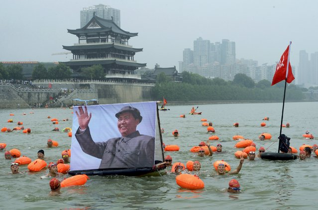 Participants wave as they swim with a portrait of late Chinese Chairman Mao Zedong in the Xiangjiang river, a large branch of the Yangtze River, in Changsha, Hunan province, China, July 18, 2015. A total of 280 residents took part in the event to celebrate the 49th anniversary of Mao swimming in the Yangtze River on July 16, 1966, local media reported. (Photo by Reuters/Stringer)