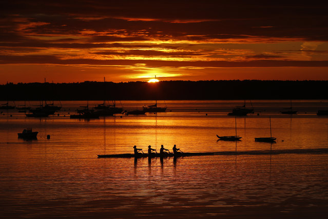 A quad scull of rowers begin their workout on Casco Bay as the sun starts to peak over Great Diamond Island, Wednesday, August 28, 2019, in Portland, Maine. Calm winds and flat water made for ideal conditions for the Portland Community Rowing Association's final outing of the year. (Photo by Robert F. Bukaty/AP Photo)