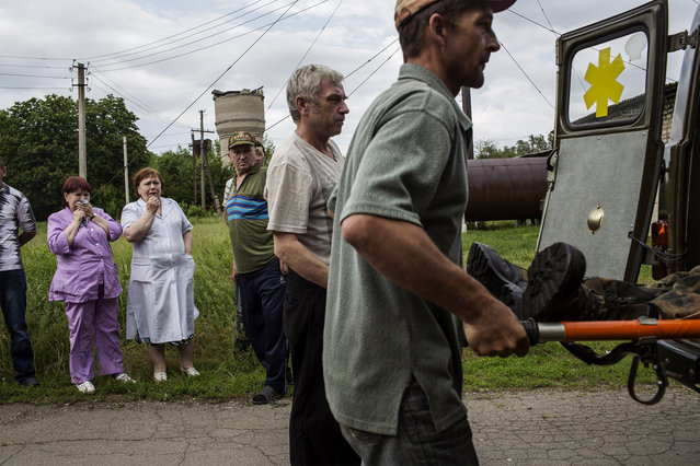 Men carry the body of a killed Ukrainian army soldier out of a van and into the morgue in Volnovakha, on May 22, 2014, after an ambush at a check point between Blohoddatne and Horlivka, 50km south of Donetsk. Pro-Russian rebels firing mortar shells and grenades killed 14 Ukrainian soldiers today, the blackest day yet for the military and a dramatic ratcheting up of tensions just three days before a crunch election. (Photo by Fabio Bucciarelli/AFP Photo)
