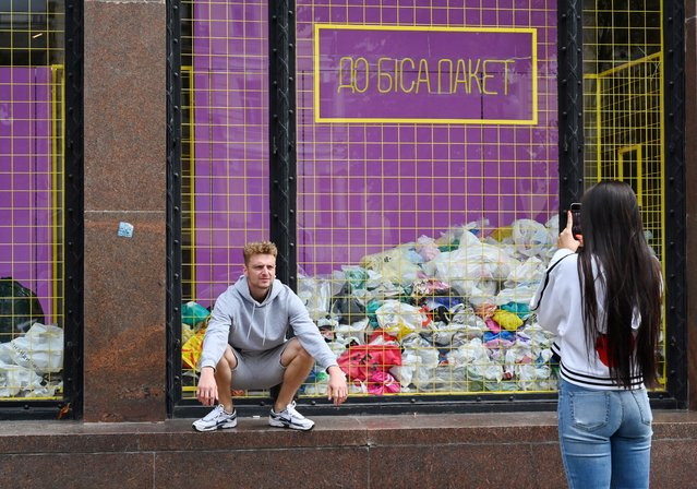 """A man poses as a woman takes a smartphone picture in front of a shop window displaying a load of used plastic bags under an inscription reading """"Go to hell with the package"""" in Kiev on September 4, 2019. The """"All locals"""" store for the first time in Ukraine refuses to use plastic bags in an effort to change the consumption behavior of the Ukrainians. The average Ukrainian uses 500 plastic bags a year on average. (Photo by Sergei Supinsky/AFP Photo)"""
