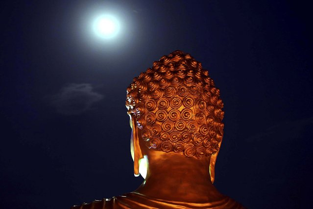 A full moon is seen behind a Buddha statue lit up on the eve of the Buddha Jayanti festival at a monastery in Bhopal, India, on May 13, 2014. The festival marks Buddha's birth, enlightenment and death. (Photo by Rajeev Gupta/Associated Press)