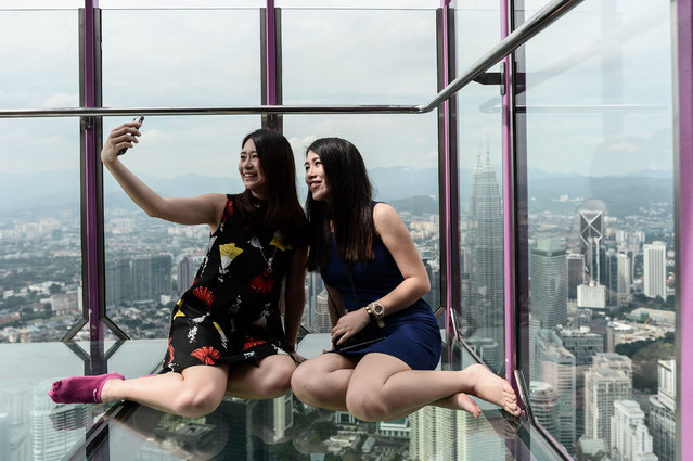 Ng Sin Nee (L) and Lee Shin May (R) from Malaysia take pictures with the panoramic view of the city from the Sky Box at KL Tower, the world's seventh tallest telecommunications tower, in Kuala Lumpur on May 24, 2016. Officially opened on May 20, the Sky Box has been the latest attraction for tourists arriving to the Malaysian capital. It stands 300 metres above ground and can fit six people at any one time, and offers spectacular views of the Kuala Lumpur skyline, including the iconic Petronas Twin Towers. (Photo by Mohd Rasfan/AFP Photo)