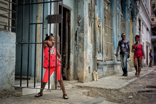 "A little girl dressed in a bright Minnie Mouse outfit and matching hairdo hangs out on her doorstep in Old Havana, Cuba, May 2, 2016. Saguy writes, ""American brands, shunned until recently as symbols of rampant consumerism, are now omnipresent in Cuban clothing"". (Photo by Dotan Saguy)"