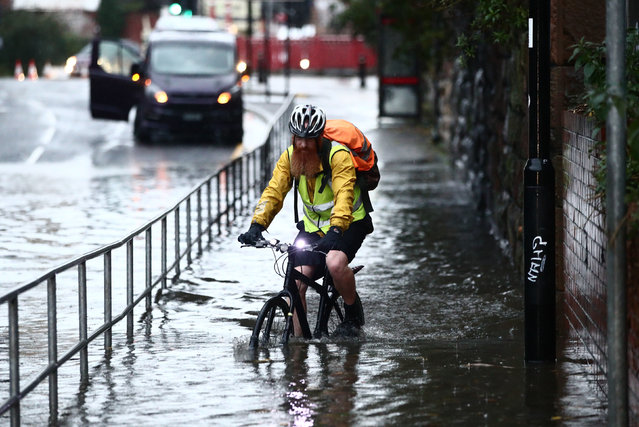 A man cycles through a flooded street Sheffield in England Thursday November 7, 2019, after torrential rain in the area. (Photo by Danny Lawson/PA Images via Getty Images)