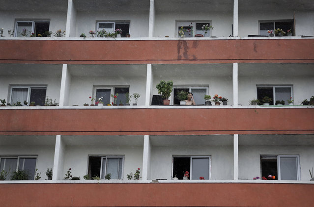 A man looks out from the balcony of his apartment, Saturday, July 25, 2015, in Ryongsong District in northern Pyongyang, North Korea. High rise apartments are a common form of accommodation for people living in Pyongyang. (Photo by Wong Maye-E/AP Photo)