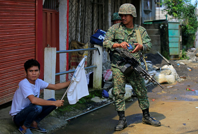 A government soldier looks at a man holding a white flag who fled his home as government troops continue their assault on insurgents from the Maute group, who have taken over large parts of the Marawi City, Philippines June 1, 2017. (Photo by Romeo Ranoco/Reuters)