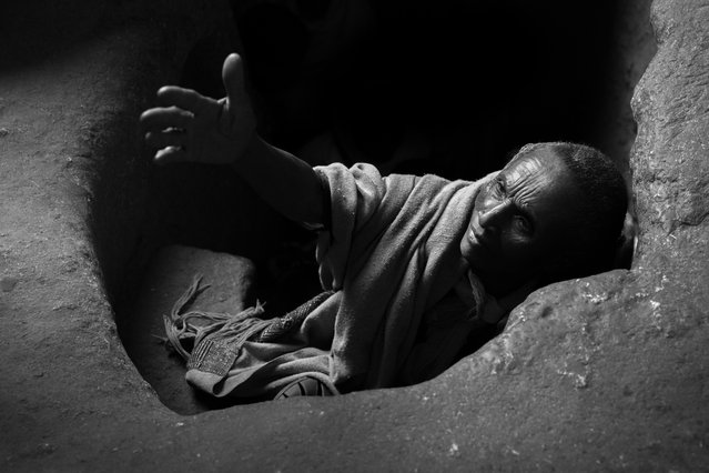"""""""Into the light"""". A pilgrim emerges from an underground tunnel that connects monolithic rock churches in Lalibela, Ethiopia. The shift from total darkness into light is believed to heal and enlighten those who pass through the tunnel. Over Orthodox Christmas in January thousands of Ethiopian pilgrims travel to Lalibela, many on foot, to partake in the ancient celebrations. Photo location: Lalibela, Ethiopia. (Photo and caption by Sarah Isaacs/National Geographic Photo Contest)"""