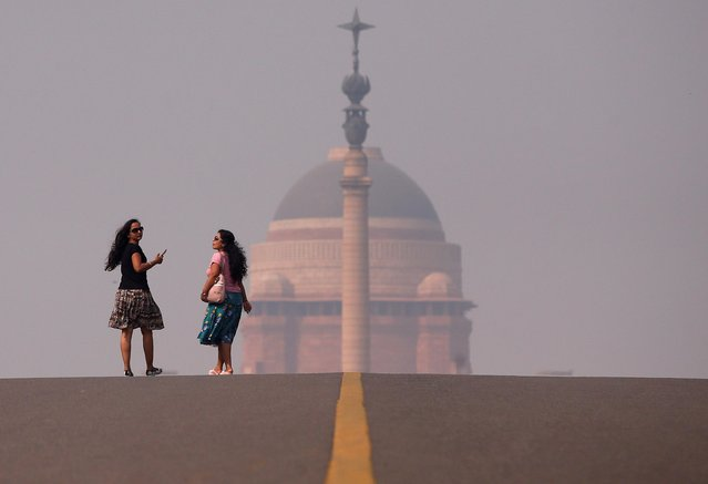 Women walk in front of India's Presidential Palace on a smoggy morning in New Delhi, India, October 27, 2019. (Photo by Altaf Hussain/Reuters)