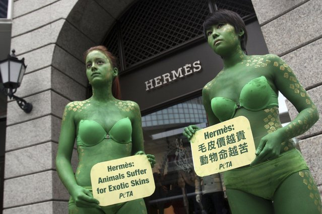 "This Thursday, October 20, 2011 file photo shows activists from People for the Ethical Treatment of Animals (PETA) Asia, with their bodies painted, holding signs against French fashion house Hermes' use of animal skins in Taipei, Taiwan. British singer Jane Birkin has asked Hermes to take her name off the crocodile-skin versions of the iconic Birkin handbag, after being contacted by animal rights group PETA over ""cruel"" slaughtering practices. (Photo by Chiang Ying-ying/AP Photo)"