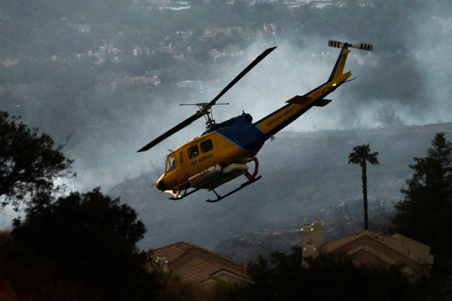 """A helicopter makes a water drop run at the """"Old Fire"""", which burned in Calabasas, California, U.S., June 4, 2016. (Photo by Gene Blevins/Reuters)"""