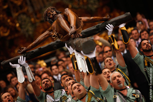 Spanish legionnaires sing an anthem as they carry a statue of the Christ of Mena during the Holy Week in Malaga, southern Spain