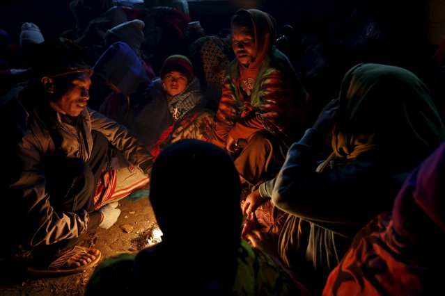 Hindu worshippers gather around a fire keep themselves warm as they wait for the Kasada Festival ceremony to commence at Mount Bromo in Probolinggo, Indonesia's East Java province, August 1, 2015. (Photo by Reuters/Beawiharta)