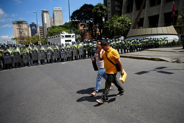 Pedestrians walk past riot police officers during a protest called by university students against Venezuela's government in Caracas, Venezuela, June 9, 2016. (Photo by Carlos Garcia Rawlins/Reuters)