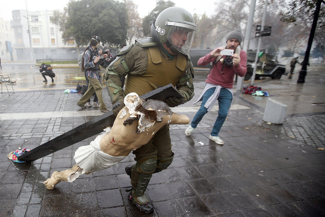 Policemen recover a cross taken from the National Gratitude Church during a protest of students days before a meeting between the Education Minister Adriana Delpiano and the Confederation of Chilean Students in Santiago de Chile, Chile, 09 June 2016. Students have been protesting for free, high-quality public education. (Photo by Mario Ruiz/EPA)