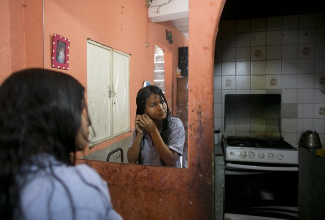 In this June 1, 2016 photo, Maria Arias stands near her kitchen as she puts on earrings while getting ready for school in Caracas, Venezuela. So many students have fainted from hunger at Maria's school that administrators told parents to keep their children home until they could find more food. (Photo by Ariana Cubillos/AP Photo)
