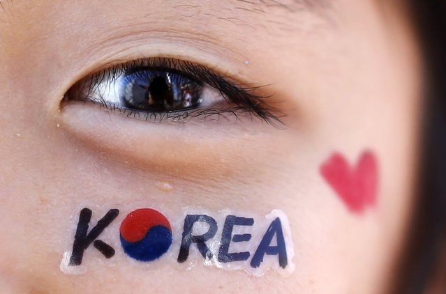 """A South Korean fan celebrates her team in Porto Alegre, on June 22, 2014. In a project called """"On The Sidelines"""" Reuters photographers share pictures showing their own quirky and creative view of the 2014 World Cup in Brazil. (Photo by Marko Djurica/Reuters)"""