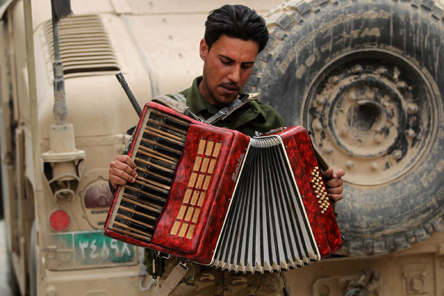An Iraqi soldier plays with an accordion found on the street while on patrol in the western neighborhood of Tamuz in Mosul on May 23, 2017, after the area was retaken during the ongoing offensive against Islamic State (IS) group fighters. (Photo by Ahmad Al-Rubaye/AFP Photo)