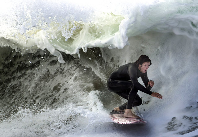 A surfer performs at the Wedge in Newport Beach, Calif., Monday, July 10, 2017. (Photo by Mindy Schauer/The Orange County Register via AP Photo)