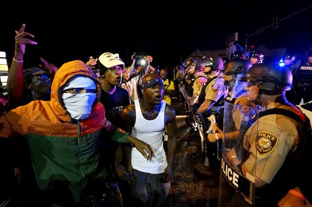 Protesters yell at a police line shortly before shots were fired in a police-officer involved shooting in Ferguson, Missouri August 9, 2015. (Photo by Rick Wilking/Reuters)
