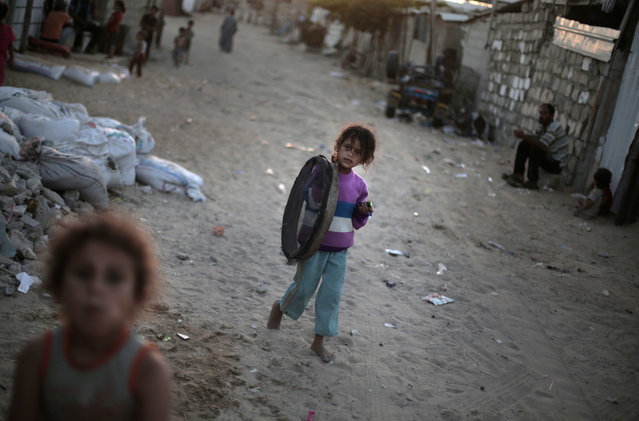 In this Monday, June 20, 2016 photo, a Palestinian girl walks barefoot in el-Zohor slum, on the outskirts of Khan Younis refugee camp, southern Gaza Strip. (Photo by Khalil Hamra/AP Photo)