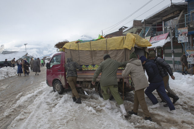 Indian police men push a load carrier stuck on a snow covered road in Kangan village, north of Srinagar, Indian controlled Kashmir, Tuesday, January 14, 2020. Severe winter weather has claimed more lives as avalanches triggered by heavy snowfall killed dozens of people in neighboring Pakistan-administered Kashmir. (Photo by Dar Yasin/AP Photo)