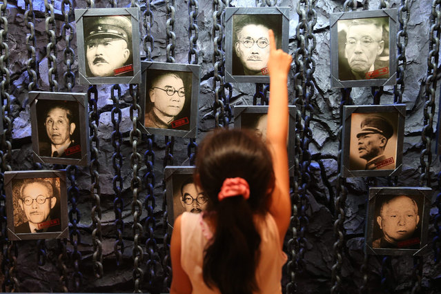 A little girl points at portraits of Japanese grade-A war criminals during an exhibition of the China Anti-Japanese War at the Military Museum in Beijing, China, 11 August 2015. The exhibition displays around 430 pictures and 515 war antiques in a 2,000 square-meter exhibition hall. Events are taking place around the World marking the 70th Anniversary of the WWII Victory over Japan Day which marks the day Japan officially accepted the terms of surrender imposed by the by Allied Forces in the Pacific conflict. (Photo by Wu Hong/EPA)