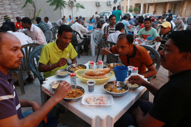 People eat their Iftar (breaking of fast) meal at tables offering free food set up by a charity during the holy fasting month of Ramadan in Benghazi, Libya,  June 29, 2016. (Photo by Esam Omran al-Fetori/Reuters)