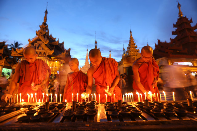 Buddhist monks light candles during the traditional Thadingyut lighting festival in Yangon, Myanmar on October 14, 2019. (Photo by U Aung/Xinhua News Agency/Barcroft Media)
