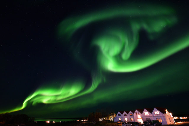 The aurora borealis, also known as northern lights, illuminates the sky along the Ring Road in southeastern Iceland, between Jokullsarlon glacier lagoon and Hofn, on October 7, 2018. (Photo by Mariana Suarez/AFP Photo)