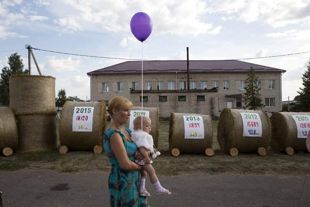 """A woman carrying a child walks in front of a display with the harvest results of recent years during the Dazhynki harvest festival in the state agricultural production cooperative """"Granit-Agro"""" in the village of Krutilovichi, southwest of Minsk, Belarus, August 22, 2015. (Photo by Vasily Fedosenko/Reuters)"""