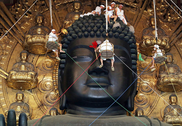 Buddhist monks and volunteers clean the 15-metre-tall great Buddha statue during the annual Ominugui ceremony at Todaiji Temple in Japan's ancient capital Nara, western Japan on August 7, 2014. People visited the temple as they believe that a person who collects the dust during the ceremony will be trouble-free for a year. (Photo by AFP Photo/JIJI Press)
