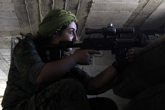 A female member of the Syrian Democratic Forces (SDF), a US backed Kurdish-Arab alliance, holds a position inside a building in an area close to the Old City in the embattled northern Syrian city of Raqa on September 3, 2017, as they battle to retake the city from the Islamic State (IS) group. (Photo by Delil Souleiman/AFP Photo)