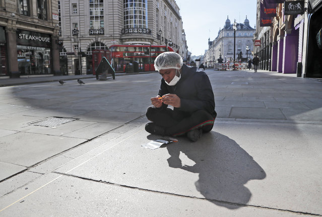 An employee of a nearby takeaway restaurant rolls a cigarette as he has a break sitting on the pavement near Piccadilliy Circus in central London, Tuesday, March 24, 2020. (Photo by Frank Augstein/AP Photo)