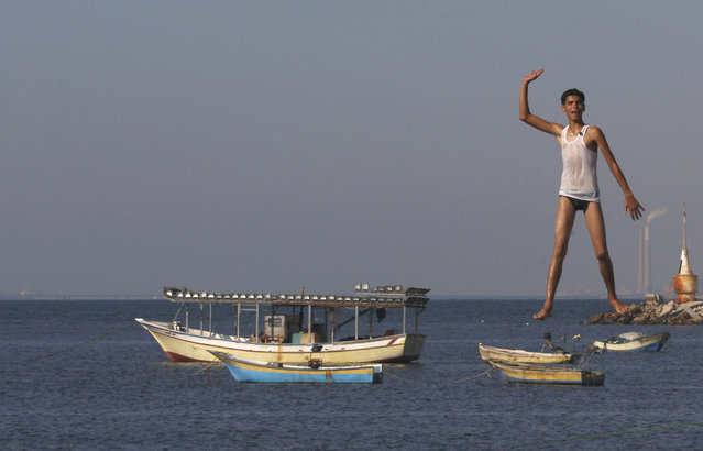 A Palestinian youth jumps into the Mediterranean sea on the beach at the port of Gaza City, Gaza, Monday, August 27, 2012. (Photo by Hatem Moussa/AP Photo)