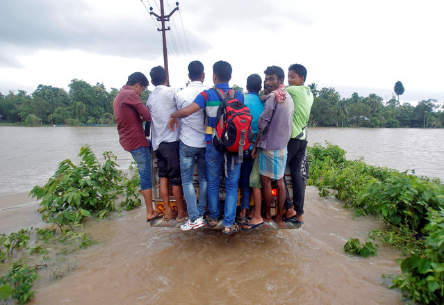 People hang onto a vehicle as they cross a flooded road after heavy rains on the outskirts of Agartala, India, July 18, 2016. (Photo by Jayanta Dey/Reuters)