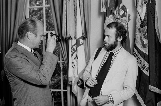 President Gerald Ford prepares to take a picture of David Hume Kennerly, 27, a Pulitzer Prize-winning photographer in the White House Oval Office in Washington, August 11, 1974. Ford named Kennerly as official White House photographer. Kennerly left his assignment with Time Magazine to replace Ollie Atkins in the post. (Photo by Charles Harrity/AP Photo)