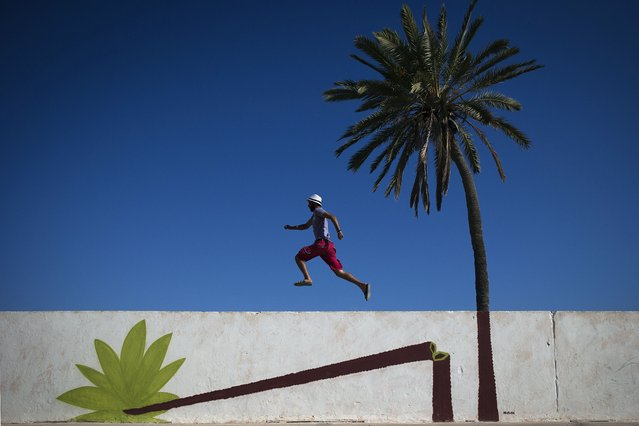 """A man runs along a mural by Polish artist M-CITY decorating a wall in the village of Erriadh, on the Tunisian island of Djerba, on August 7, 2014, as part of the artistic project """"Djerbahood"""". (Photo by Joel Saget/AFP Photo)"""