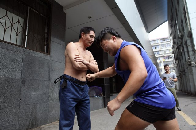 Xie Shuiping (L) is punched by an athlete as part of a challenge in Nanchang, Jiangxi province, August 18, 2014. Xie, 48, has been challenging people to punch his belly for more than ten years. He has promised to give the challenger 1,000 yuan ($163) if they can make him fall or step back from being punched but only one person has managed to do so thus far, according to local media. (Photo by Reuters/Stringer)