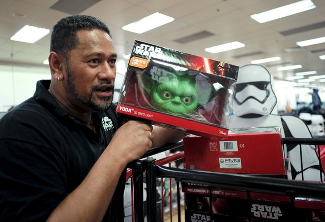 """Actor Jay Laga'aia, who plays Captain Typho in the two most recently-released Stars Wars films, helps stock a department store with Yoda decorator lights from the upcoming film """"Star Wars: The Force Awakens"""" just before midnight on """"Force Friday"""", September 4, 2015. (Photo by Jason Reed/Reuters)"""