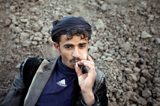 A labourer smokes a cigarette as he rests at a brick factory on the outskirt of Sanaa, Yemen, June 1, 2016. (Photo by Mohamed al-Sayaghi/Reuters)