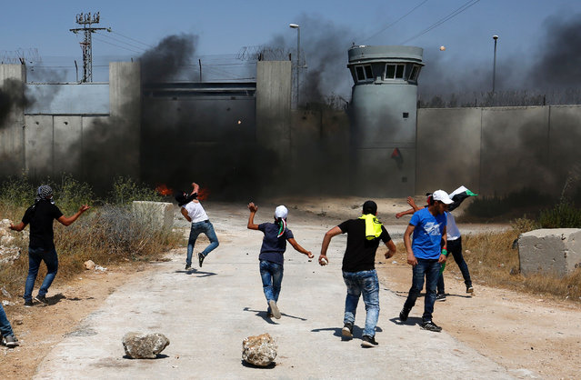 Palestinian youths burn tires and throw stones towards an Israeli military post following the Friday prayer on July 29, 2016 near Qalandia, which is located next to Israel's controversial separation barrier, between the West Bank town of Ramallah and East Jerusalem, three days after Palestinian homes were destroyed by Israeli authorities. On July 26, 2016, Israeli authorities demolished a dozen Palestinian homes in Qalandia, according to Palestinian sources. Witnesses added that shortly after midnight, a convoy of dozens of military vehicles and Israeli bulldozers stormed the area, before demolishing 11 houses. (Photo by Abbas Momani/AFP Photo)