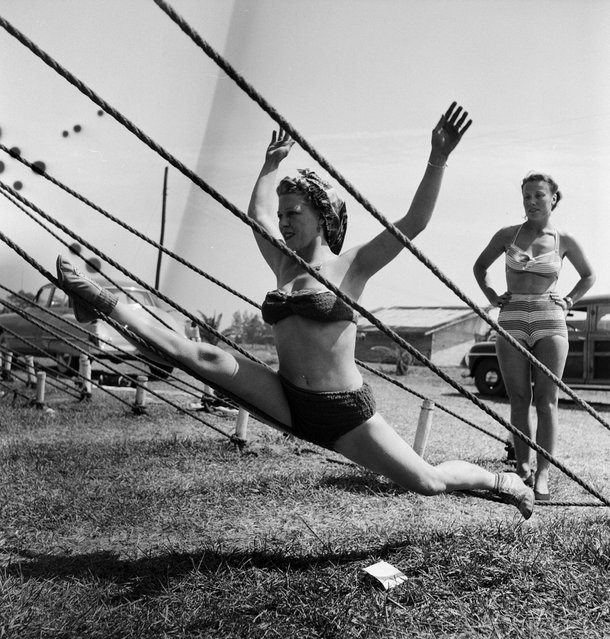 An acrobat practicing on a tent rope while an unidentified woman is standing nearby during a rehearsal for the Ringling Bros. and Barnum & Bailey Circus in Sarasota, FL in 1949. (Photo By Nina Leen/Time Life Pictures/Getty Images)
