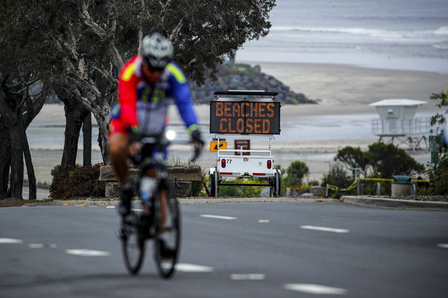A cyclist rides past a closed beach sign during the outbreak of the coronavirus disease (COVID-19) in Del Mar, California, U.S. April 30, 2020. (Photo by Mike Blake/Reuters)